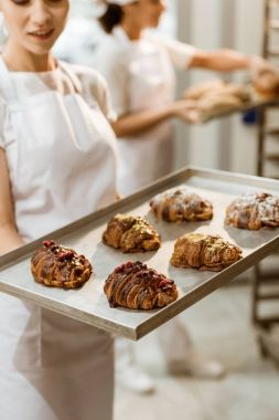 close-up shot of young baker holding tray with fresh croissants at baking manufacture