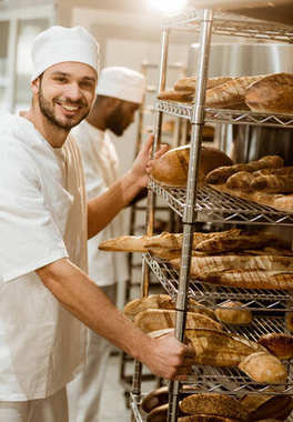 baker near shelves with fresh bread loaves at baking manufacture