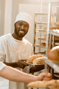 smiling african american baker holding loaves of bread on tray at baking manufacture