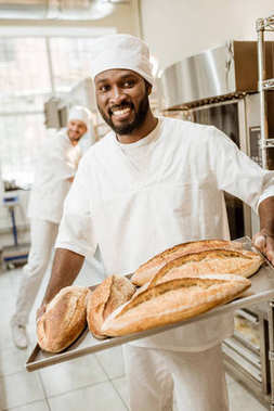 african american baker taking bread loaves from oven at baking manufacture