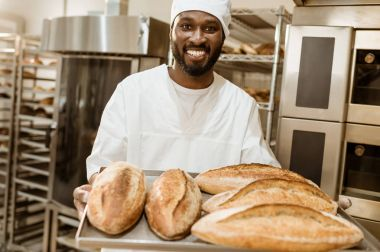 handsome african american baker with tray of fresh loaves of bread on baking manufacture