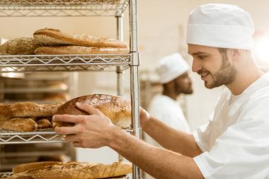 handsome smiling  baker putting fresh bread loaf on shelf at baking manufacture