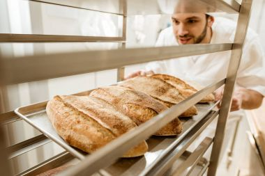 close-up shot of handsome baker putting trays of fresh bread on stand at baking manufacture