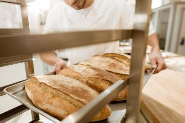 cropped shot of baker putting trays of fresh bread on stand at baking manufacture