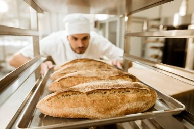 young baker putting trays of fresh bread on stand at baking manufacture