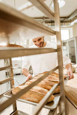 happy young baker putting trays of fresh bread on stand at baking manufacture
