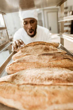 excited african american baker looking at fresh loaves of bread on baking manufacture