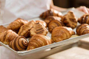 cropped shot of baker holding tray with fresh croissants on baking manufacture