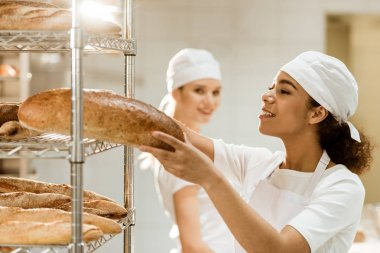 female baker putting fresh bread loaves on shelves at baking manufacture while her colleague standing blurred on background