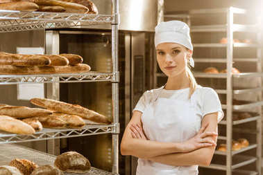 young female baker with crossed arms near shelves with freshly baked bread on baking manufacture