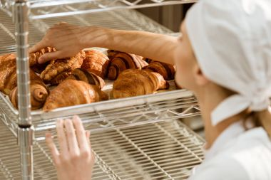 close-up shot of female baker doing examination of freshly baked croissants on baking manufacture
