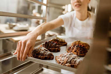 cropped shot of female baker holding tray of freshly baked croissants on baking manufacture