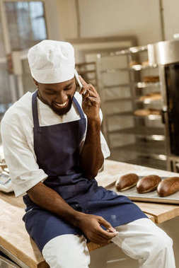 young african american baker with hands covered in flour talking by phone while sitting on work table