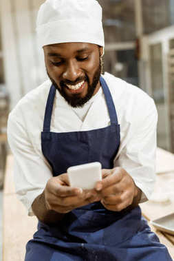 young african american baker with hands covered in flour using smartphone