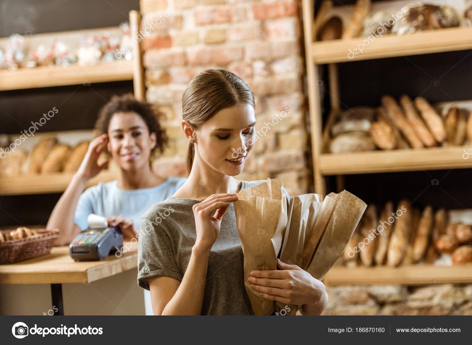 Lächelnde Junge Frau Verlassen Pastry Shop Mit Verschiedenen Brot