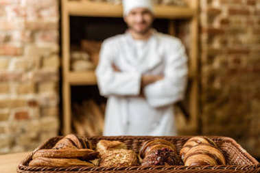 blurred baker with crossed arms standing at pastry store with basket of croissants on foreground