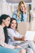 Fotografie Smiling women using tablet in wedding salon