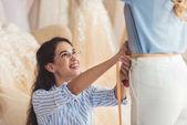 Krejčí, měření pasu klientku v svatební módou