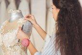 Fotografia Sarta fissaggio pizzo abito in negozio di moda sposa