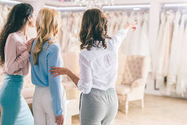 Female friends looking at dresses in wedding fashion shop