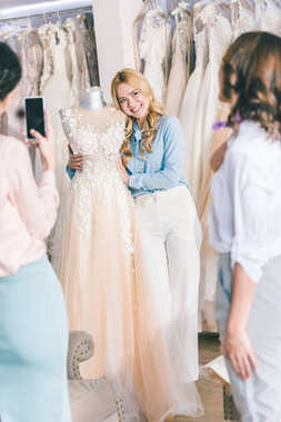 Bridesmaids and bride taking photo while choosing dress in wedding fashion shop
