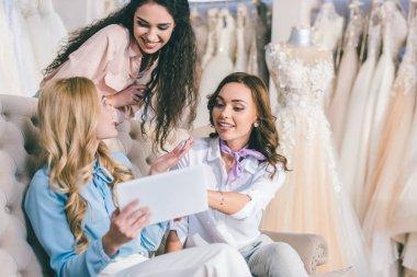 Attractive women choosing wedding dress and looking at tablet in wedding atelier