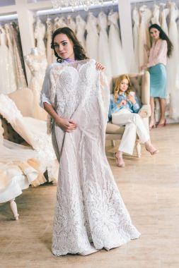 Attractive woman in wedding dresses and bridesmaid in wedding salon stock vector