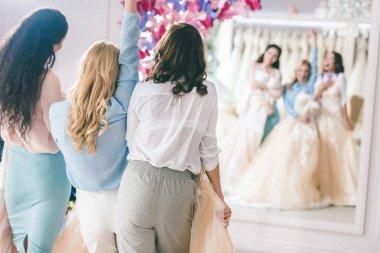 Attractive bride and bridesmaids by mirror in wedding fashion shop