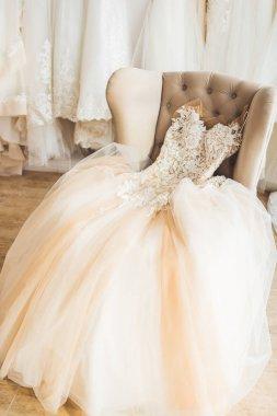 Lace wedding dress on chair in wedding salon