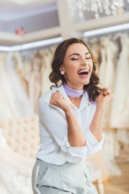 Laughing young woman in wedding fashion shop