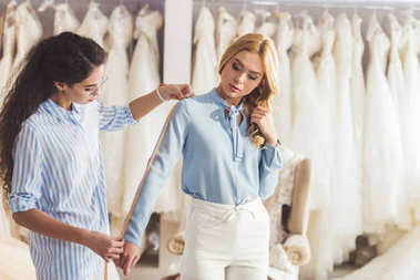 Young woman and professional tailor taking measurements in wedding fashion shop
