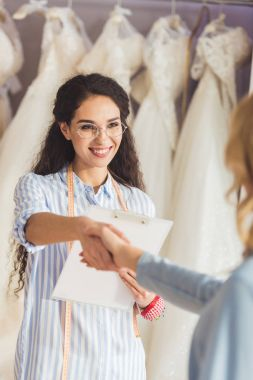 Female tailor and bride shaking hands in wedding fashion shop
