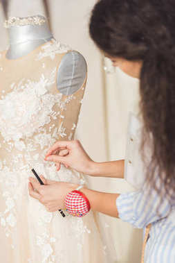 Seamstress working by beautiful dress in wedding atelier
