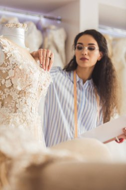 Tailor attaching decorative details to dress in wedding salon