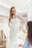 Fotografie Bride in lace dress and tailor in wedding salon