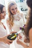 Nevěsta s přáteli drží šampaňské sklenice a láhev v svatební salon
