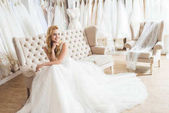 Fiatal menyasszony tüll ruha ül kanapén esküvői szalonban