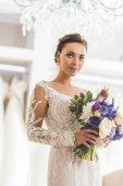 Krásná nevěsta s květinovým buketem v svatební atelier