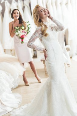 Young bride and friend in wedding fashion shop