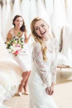 Smiling women in wedding dresses with flowers in wedding salon