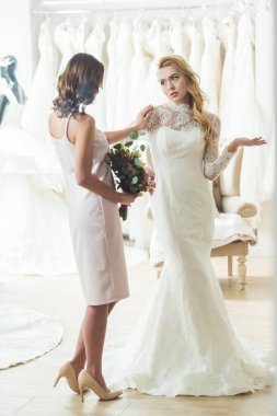 Upset bride with friend in wedding fashion shop