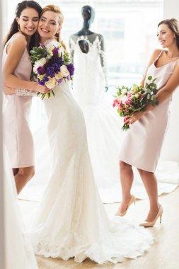 Smiling women in wedding dresses embracing in wedding fashion shop
