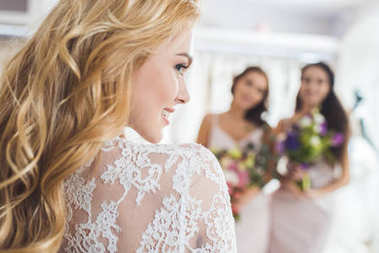 Bride in lace dress and bridesmaids with flowers in wedding fashion shop