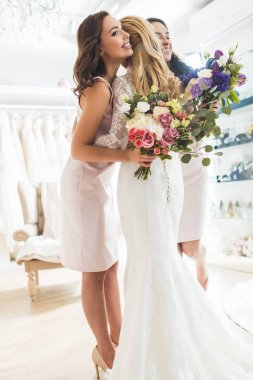 Smiling women in wedding dresses embracing in wedding atelier
