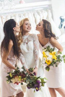 Attractive women in wedding dresses kissing in wedding salon