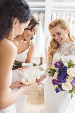 Attractive women in wedding dresses pouring champagne in wedding fashion shop