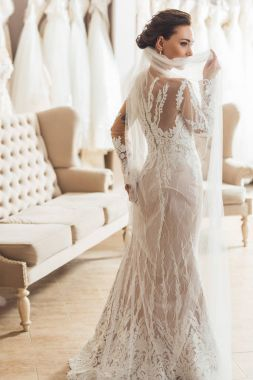 Attractive woman wearing wedding dress in wedding fashion shop