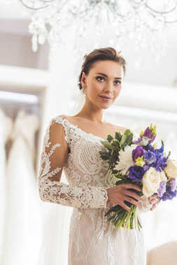 Beautiful bride with floral bouquet in wedding atelier