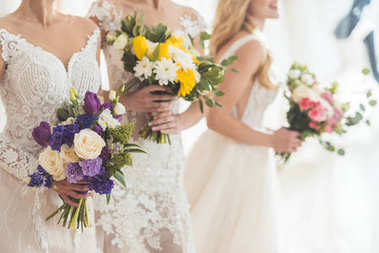 Close-up view of brides in lace dresses with flowers in wedding fashion shop
