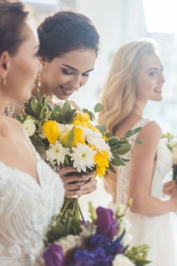 Young brides holding tender flowers bouquets in wedding salon
